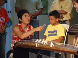 琴を前にした男の子に、マイクを向ける中井智弥さん