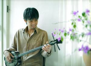 三線を弾き微笑む池田卓さん