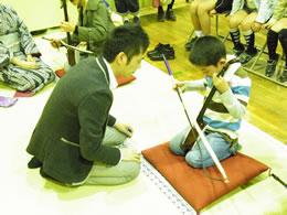 日本の擦弦楽器・胡弓を体験する少年と指導する若手奏者・木場大輔さん